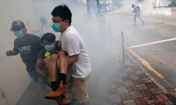 Anti-government protesters run away from tear gas during a march against Beijing's plans to impose national security legislation in Hong Kong on May 24, 2020. (Tyrone Siu/Reuters)