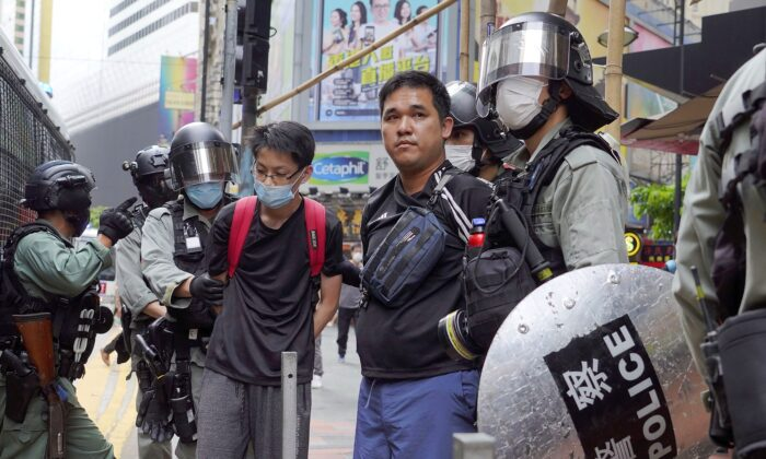 Riot police detain protesters in Causeway Bay, Hong Kong, as hundreds took to the streets to march against Beijing's proposed tough national security legislation for the city, on May 24, 2020. (AP Photo/Vincent Yu)