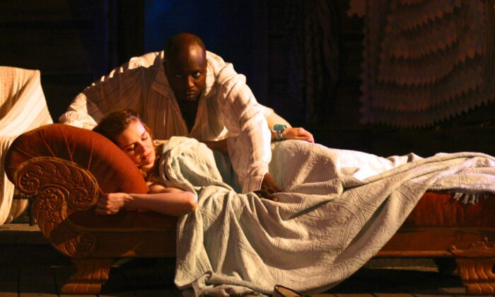 """The cunning Iachimo (Jeff Award-nominee James Earl Jones II) steals into the bed chamber of innocent Imogen (Kate McDermott) to defame her character, First Folio Theatre's 2013 production of """"Cymbeline,"""" available for online viewing. (D. Rice)"""