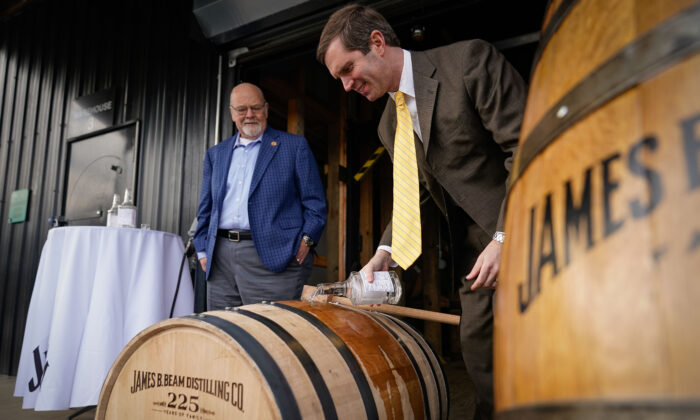 Kentucky Gov. Andy Beshear (R) fills Jim Beam Distillery's 16 millionth barrel of bourbon, as Master Distiller Fred Noe looks on, at the Jim Beam Distillery in Clermont, Ky., on Feb. 17, 2020. (Bryan Woolston/Getty Images)