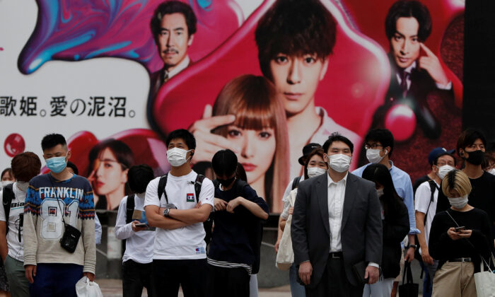 Passersby wearing protective masks are seen as the spread of the CCP virus continues, at Shibuya crossing in Tokyo on May 25, 2020. (Issei Kato/Reuters)