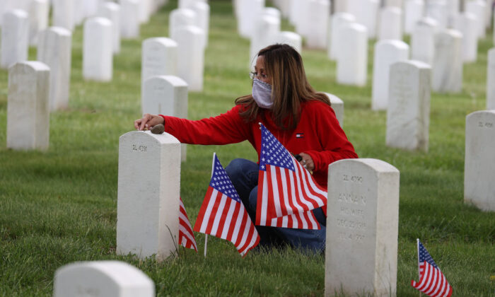 Louise Lombardi of Baldwin, N.Y., visits the gravesite of her father, Joseph Lombardi, who was a World War II veteran, at Long Island National Cemetery in Farmingdale, N.Y., on May 24, 2020. (Al Bello/Getty Images)