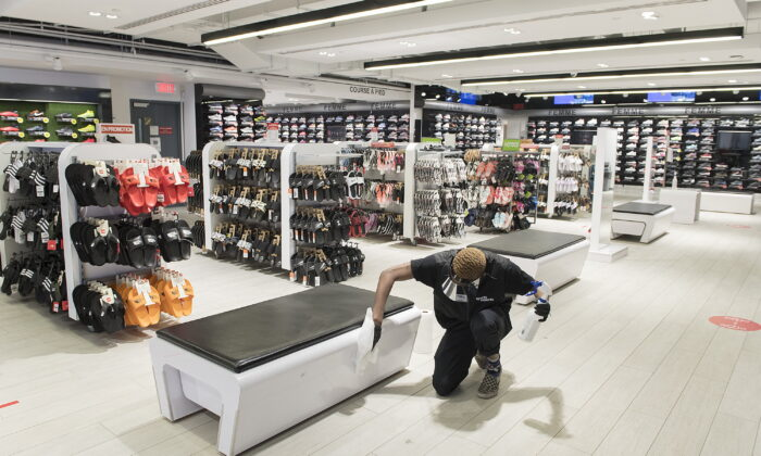 Liam Slater Oda, an employee with Sports Experts disenfects a bench at the store on Sainte-Catherine street in Montreal, on May 24, 2020. THE CANADIAN PRESS/Graham Hughes