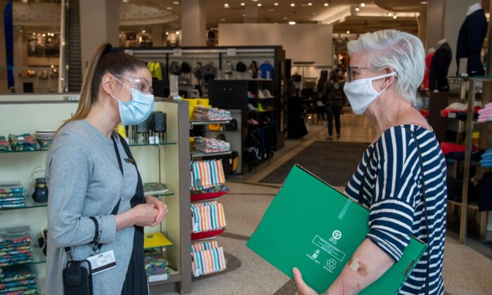A store employee explains health safety procedures to a customer in Montreal May 25, 2020. (Sebastien St-Jean/AFP via Getty Images)