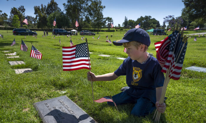 Ethan Burdzinski, 6, places flags on a veterans grave in the Pierce Brothers memorial park in Westlake on May 23, 2020 in Los Angeles, California. (Photo by Brent Stirton/Getty Images)