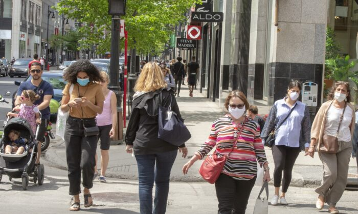People walk along Sainte-Catherine Street in Montreal as many non-essential businesses are allowed to re-open, on May 25, 2020. (The Canadian Press/Ryan Remiorz)