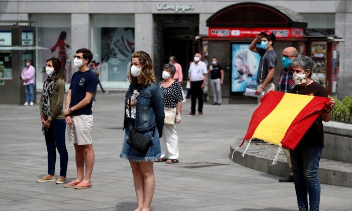 People wearing protective face masks stand during a daily minute of silence to commemorate victims of the CCP Virus, at Puerta del Sol square in Madrid, Spain, on May 26, 2020. (Sergio Perez/Reuters)