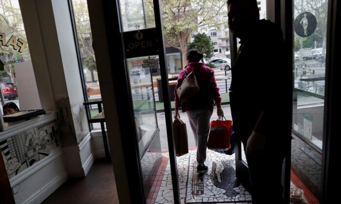 An employee of Farley's East Cafe, which closed due to the financial crisis caused by the CCP virus, carries donated food items after being laid off from the cafe in Oakland, Calif., on March 18, 2020. (Shannon Stapleton/Reuters)