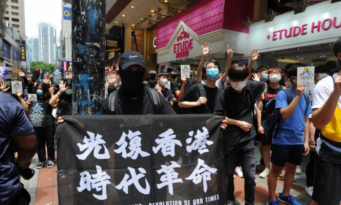 "A protester holds up a banner with the words ""Liberate Hong Kong, Revolution of Our Time"" at a protest in Causeway Bay, Hong Kong, on May 24, 2020. (Song Bilung/The Epoch Times)"