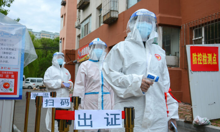 Staff waiting to check people's entering permit, screen their body temperature, and scan their health codes at the entrance of a residential compound in Jilin city, China, on May 25, 2020. (STR/AFP via Getty Images)