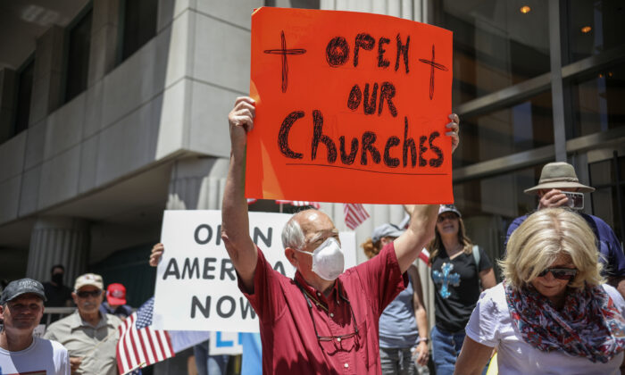 Demonstrators holding signs demanding their church to reopen, protest during a rally to reopen California and against stay-at-home directives San Diego, California, on May 1, 2020. (Sandy Huffaker/AFP via Getty Images)