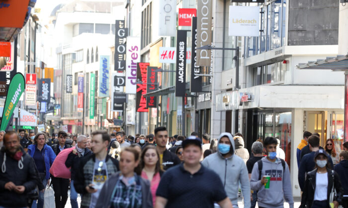 People walk past shops in the shopping street Hohe Straße during the coronavirus crisis on May 23, 2020 in Cologne, Germany. (Andreas Rentz/Getty Images)