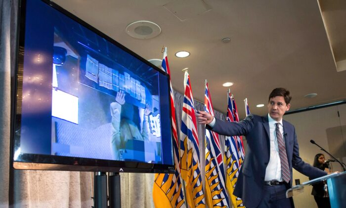 B.C. Attorney General David Eby gestures while showing a video of bundles of cash brought to a casino by an individual, during a news conference in Vancouver on June 27, 2018. An inquiry into money laundering in B.C. resumed this week. (The Canadian Press/Darryl Dyck)