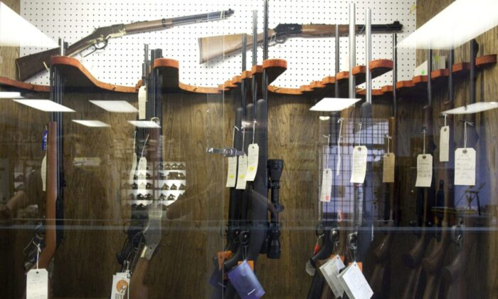 Hunting rifles are seen on display in a glass case at a gun and rifle store in downtown Vancouver in this file photo. (Jonathan Hayward/The Canadian Press)