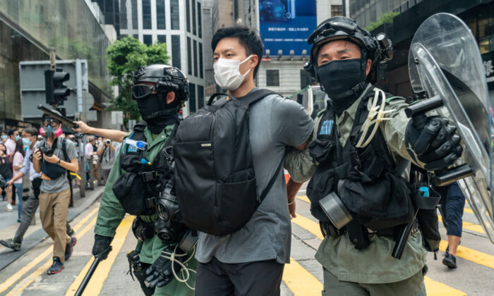 A pedestrian is detained by riot police during a Lunch with You rally in Central district in Hong Kong on May 27, 2020. (Anthony Kwan/Getty Images)