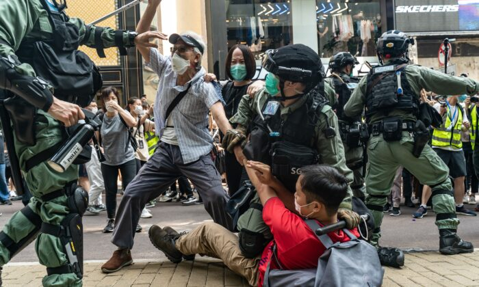 Pro-democracy supporters scuffle with riot police during a detention at a rally in the Causeway Bay district in Hong Kong, on May 27, 2020. (Anthony Kwan/Getty Images)