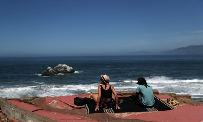 A couple sits on a rock overlooking Ocean Beach in San Francisco, Calif. on May 26, 2020. (Justin Sullivan/Getty Images)