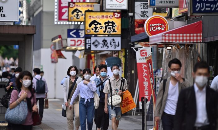 Two days after the Japanese government lifted a state of emergency due to the COVID-19, people wearing face masks walk in a street in Tokyos Akihabara area, Japan, on May 27, 2020. (Charly Triballeau / AFP via Getty Images)