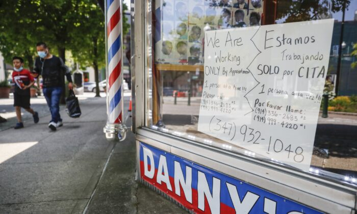 Pedestrians pass a barbershop that displays a sign advertising haircuts by appointment only in New Rochelle, N.Y., on May 26, 2020. (John Minchillo/AP Photo)