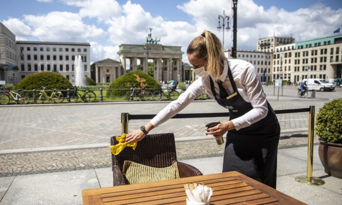 A waitress disinfects a  table in a restaurant at the Hotel Adlon Kempinski next to the Brandenburg Gate in Berlin on May 26, 2020. (Maja Hitij/Getty Images)