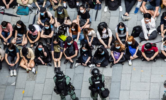 Riot police detain a group of people during a protest in the Causeway Bay district of Hong Kong on May 27, 2020, as the city's legislature debates over a law that bans insulting China's national anthem. (Isaac Lawrence/AFP via Getty Images)