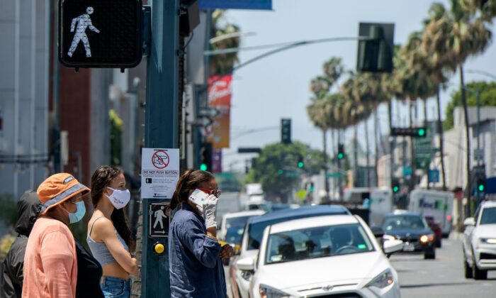 People wait to cross the street on Rodeo Drive, where a sign is displayed asking the pedestrian not to push the button, amid the COVID- 19 pandemic in Beverly Hills, Calif., May 26, 2020 (Valerie Macon/AFP via Getty Images)