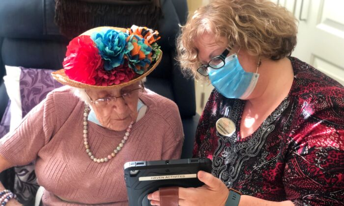 Joanne Hubbard, executive director at Kensington Place, helps a resident use a device. (Andrea Obston/Courtesy of Kensington Place)