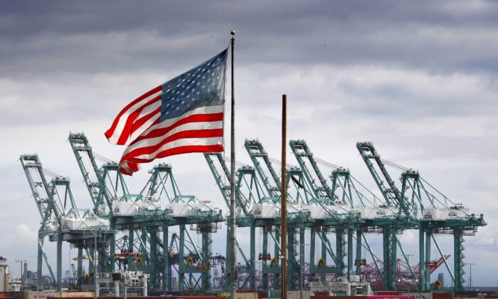 The U.S. flag flies over shipping cranes and containers in Long Beach, Calif., on March 4, 2019. (Mark Ralston/AFP via Getty Images)