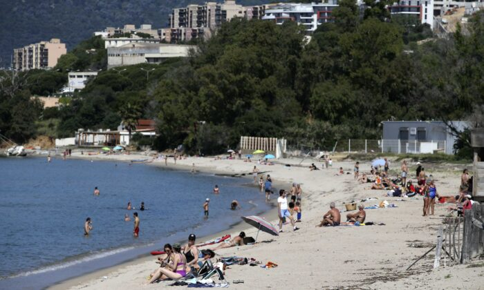People enjoy the Ricanto beach in Ajaccio on May 21, 2020 as nearly all island beaches reopened on the French Mediterranean island of Corsica. (Pascal Pochard-Casabianca/AFP via Getty Images)