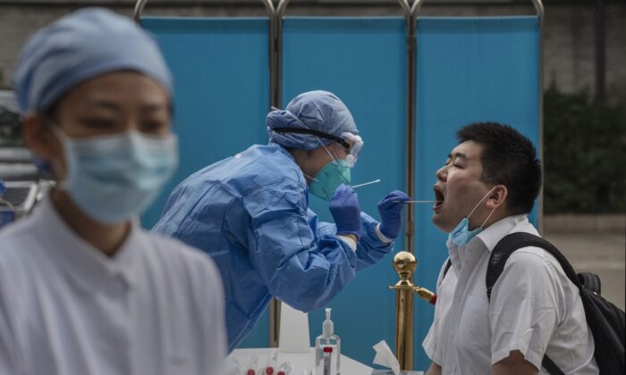 A Chinese health worker carries out a nucleic acid test on a journalist covering events around the National People's Congress in Beijing, China on May 28, 2020. (Kevin Frayer/Getty Images)