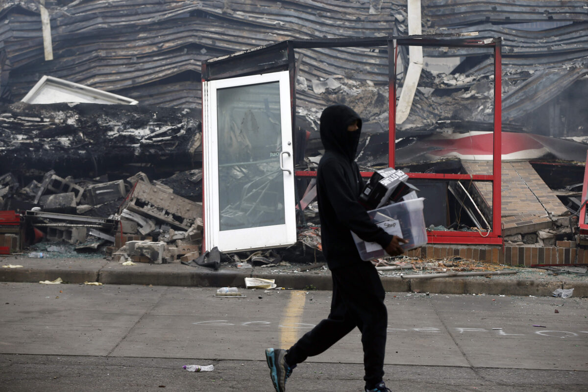 A man carries items past a burned out Auto Zone store