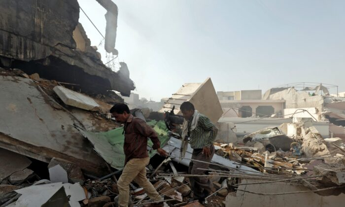 Men walk on the debris at the site of a passenger plane crash in a residential area near an airport in Karachi, Pakistan, on May 22, 2020. (Akhtar Soomro/File Photo/Reuters)