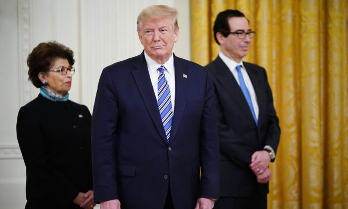 President Donald Trump is flanked by SBA Administrator Jovita Carranza (L) and Treasury Secretary Steven Mnuchin, at a briefing at the White House in Washington, on April 28, 2020. (Mandel Ngan/AFP/Getty Images)
