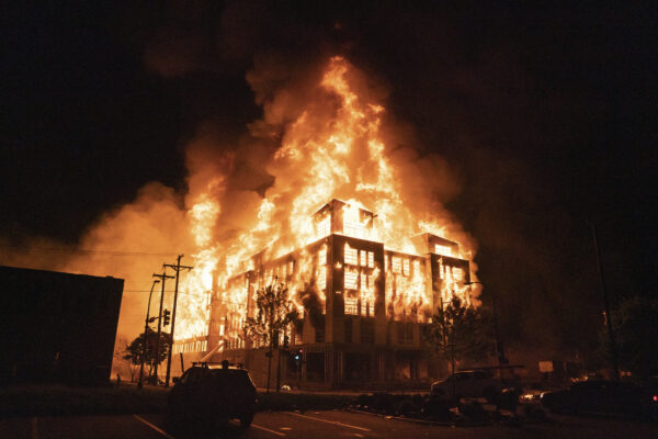 A multi-story affordable housing complex burns