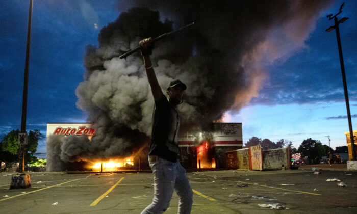 A man poses for a photo in the parking lot of an AutoZone store in flames, while protesters hold a rally for George Floyd in Minneapolis on May 27, 2020. (Carlos Gonzalez/Star Tribune via AP)