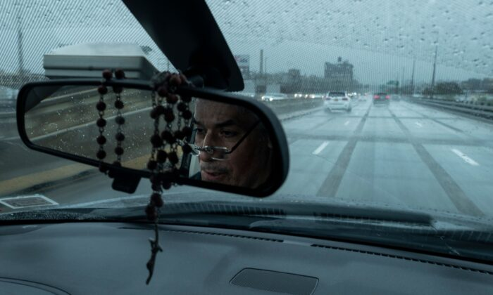 Fabian Arias, a Lutheran pastor with Saint Peter's Church is reflected as he drives his car in Brooklyn, New York City, on May 22, 2020. (Johannes Eisele/AFP via Getty Images)