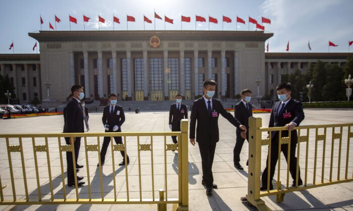 Security personnel close the gates in front of the Great Hall of the People after the closing session of China's National People's Congress in Beijing on May 28, 2020. (AP Photo/Mark Schiefelbein)