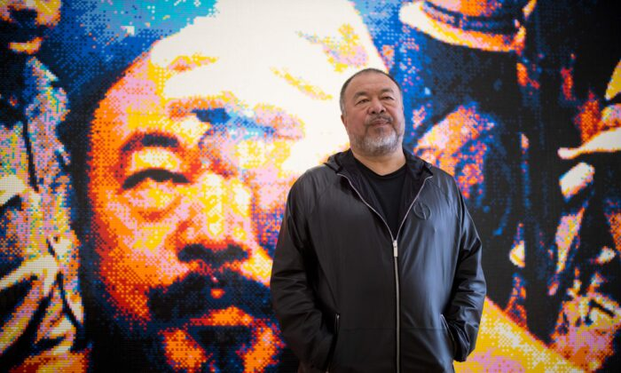 """Chinese artist Ai Weiwei poses with his artwork made of Lego, entitled """"Illumination 2019"""" during a photocall to promote his exhibition 'Roots' at the Lisson Gallery in London, England, on Oct. 1, 2019. (Tolga Akmen/AFP/Getty Images)"""