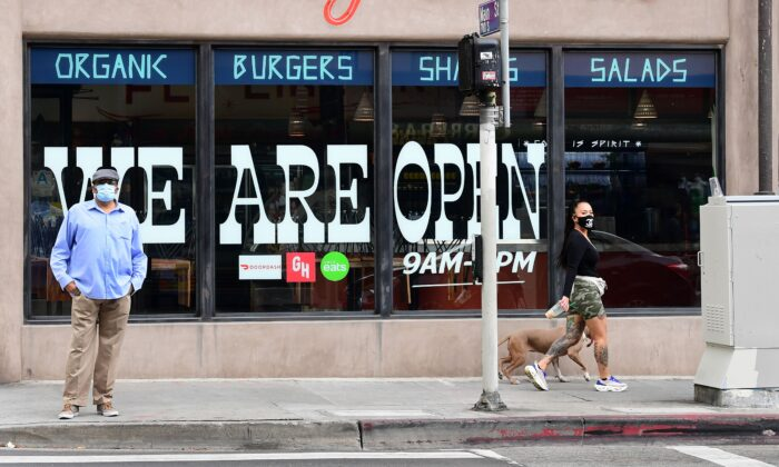 Pedestrians wear protective masks in front of a restaurant in Los Angeles, Calif., on May 12, 2020. (Frederic J. Brown/AFP/Getty Images)