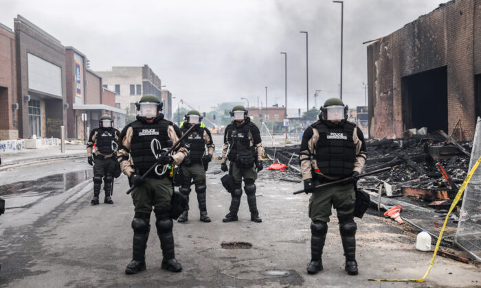Police officers stand near burned out buildings in the aftermath of a night of protests and violence following the death of George Floyd, in Minneapolis, Minn., on May 29, 2020. (Charlotte Cuthbertson/The Epoch Times)