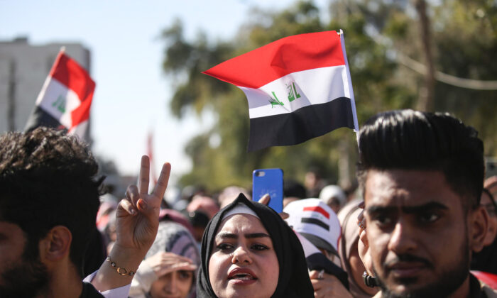 Anti-government protesters chant slogans as they march with national flags during a demonstration in the central Iraqi holy shrine city of Karbala on Jan. 26, 2020. (Mohammed Sawaf/AFP via Getty Images)