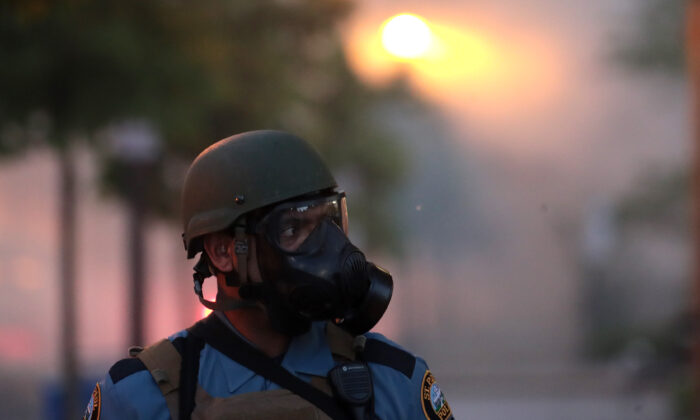 A police officer stands near a cloud of tear gas during a protest in St. Paul, Minnesota, on May 28, 2020. Today marks the third day of ongoing protests after the police killing of George Floyd. Four Minneapolis police officers have been fired over the death. (Scott Olson/Getty Images)