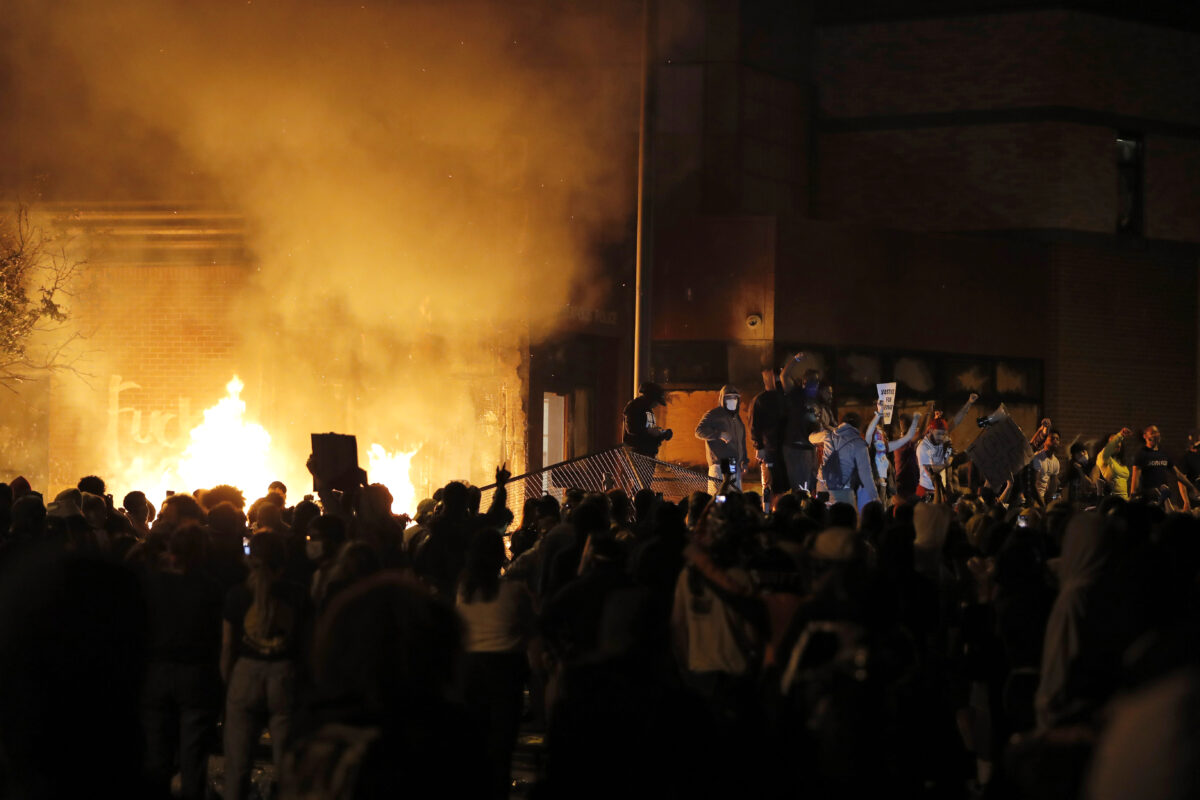 Protesters gather in front of the burning 3rd Precinct