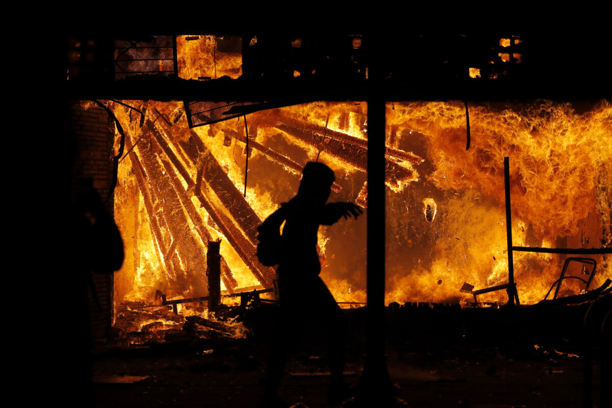 A protester is seen in front of the burning 3rd Precinct of the Minneapolis Police Department