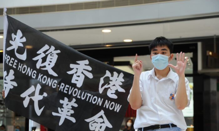"""A protester stands next to a flag with the words """"Free Hong Kong, Revolution Now"""" at a protest at the IFC shopping mall in Hong Kong on May 29. 2020. (Song Bilung/The Epoch Times)"""