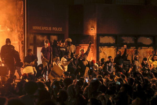 Protesters gather around after setting fire to the entrance of a police station as demonstrations continue in Minneapolis