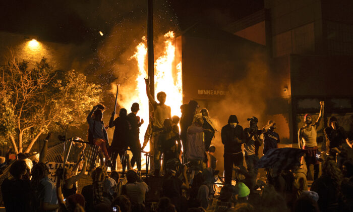 Rioters cheer as the Third Police Precinct burns behind them in Minneapolis, Minn., on May 28, 2020. (Stephen Maturen/Getty Images)