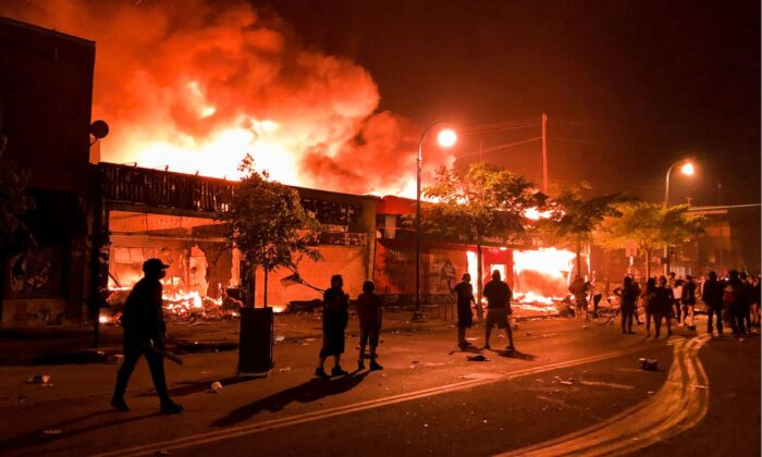 Flames rise from a liquor store and shops near the Third Police Precinct in Minneapolis, Minn., on May 28, 2020. (Kerem Yucel/AFP via Getty Images)