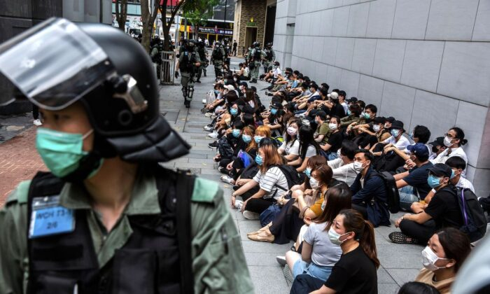 Riot police detain a group of people during a protest in the Causeway Bay district of Hong Kong as the city's legislature debates over a law that bans insulting China's national anthem on May 27, 2020. (Isaac Lawrence/AFP via Getty Images)