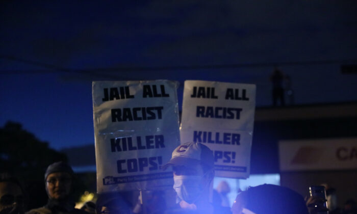 Protesters hold signs outside the Minneapolis Police 5th Precinct during the fourth night of protests and violence following the death of George Floyd, in Minneapolis, Minn., on May 29, 2020. (Charlotte Cuthbertson/The Epoch Times)